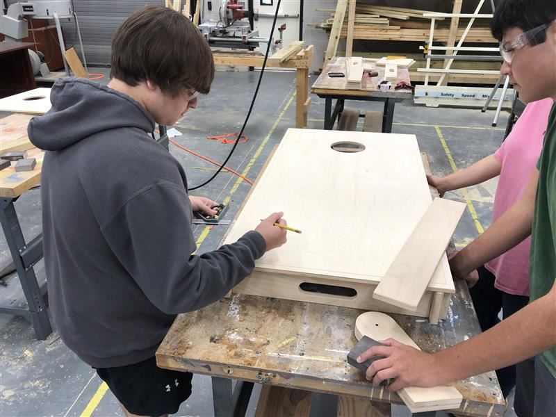 Image of students measuring a cornhole board.