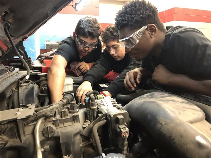Image of three students working on a car engine