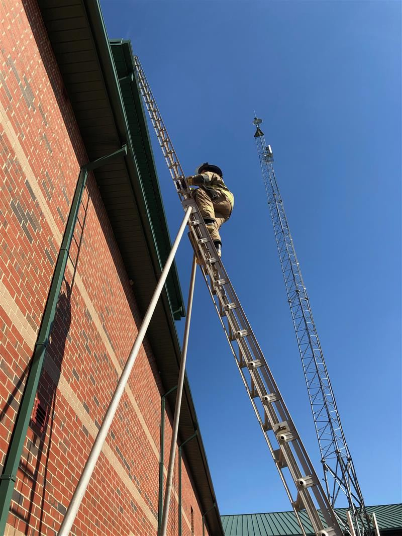 Image of a student in firefighting gear climbing a ladder