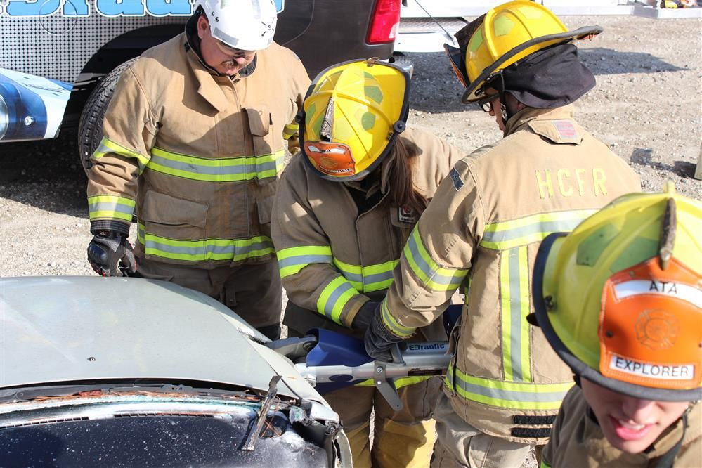Photo of students using extraction tools to open a car door.